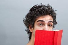 Étudiant universitaire affichant un livre intéressant Photo stock