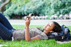 Étudiant universitaire asiatique écoutant la musique photo stock