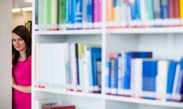 Étudiant universitaire assez jeune dans une bibliothèque photo stock