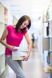 Étudiant universitaire assez jeune dans une bibliothèque photos stock