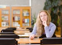 Étudiant universitaire assez jeune dans une bibliothèque regarder l'appareil-photo Photos libres de droits