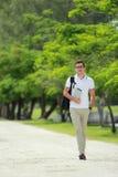 Étudiant universitaire bel marchant par au parc d'université avec le backpac Photo libre de droits