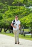 Étudiant universitaire bel marchant par au parc d'université avec le backpac Photos libres de droits