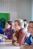 Étudiant universitaire bel s'asseyant dans une salle de classe complètement des étudiants Images libres de droits
