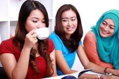 Étudiant universitaire buvant une tasse de thé et lisant un livre Photos stock