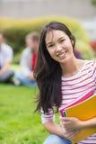 Étudiant universitaire de sourire avec les amis brouillés en parc Photographie stock