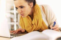 Étudiant universitaire employant l'Internet pour étudier images stock