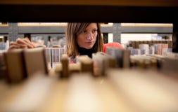 étudiant universitaire féminin dans un llibrary Photos stock