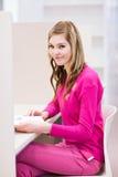 Étudiant universitaire féminin dans une bibliothèque Images stock
