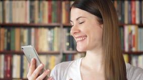 Étudiant universitaire féminin employant le mobile à la bibliothèque universitaire, passant en revue, lisant, causant avec des am banque de vidéos