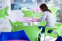 Étudiant universitaire féminin faisant le campus de homeworkon Photos stock