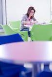 Étudiant universitaire féminin faisant le travail Photos stock