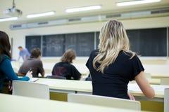 Étudiant universitaire féminin s'asseyant dans une salle de classe Photos stock