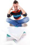 Étudiant universitaire fatigué avec la pile de livres d'isolement Photo libre de droits