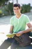 Étudiant universitaire masculin Sitting On Bench avec le livre Photos stock