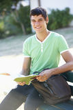 Étudiant universitaire masculin Sitting On Bench avec le livre photographie stock