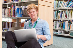 Étudiant universitaire masculin Studying In Library avec l'ordinateur portable images stock