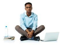 Étudiant universitaire sérieux d'afro-américain avec l'ordinateur portable, livres et Photo libre de droits