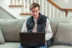 Étudiant universitaire s'asseyant sur le divan utilisant l'ordinateur portable image stock