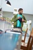 Étudiant volant l'ordinateur portatif dans la bibliothèque Photos libres de droits