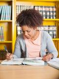 Étudiant Writing In Book à la bibliothèque Photo libre de droits
