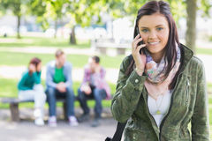 Étudiante à l'aide du téléphone portable avec les étudiants brouillés dans le parc Photographie stock