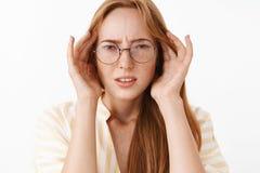 Étudiante élégante belle naïve et perplexe intéressée en verres fronçant les sourcils et louchant tenant des mains dessus photos stock