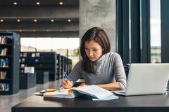 Étudiante étudiant à la bibliothèque universitaire photo libre de droits