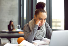 Étudiante étudiant dans la bibliothèque avec un ordinateur portable Photo stock