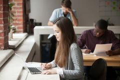 Étudiante étudiant pour des examens utilisant l'ordinateur portable photo libre de droits