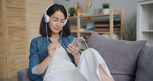 Étudiante appréciant la musique par des écouteurs touchant l'écran de smartphone clips vidéos