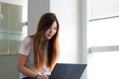 Étudiante asiatique travaillant sur un ordinateur portable souriant presque en construisant Images libres de droits