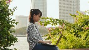 Étudiante asiatique vietnamienne à l'aide de l'ordinateur portable au centre de la ville clips vidéos