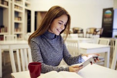 Étudiante attirante causant avec des amis par l'intermédiaire de l'application Photos libres de droits
