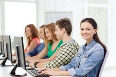 Étudiante avec des camarades de classe dans la classe d'ordinateur Photo stock