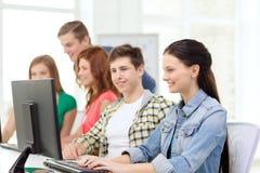 Étudiante avec des camarades de classe dans la classe d'ordinateur Image stock