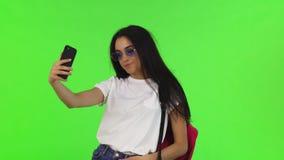 Étudiante avec du charme avec un sac à dos prenant des selfies avec son téléphone intelligent image stock