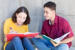 Étudiante caucasienne apprenant avec l'étudiant masculin latin image stock