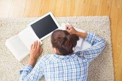 Étudiante de brune se trouvant sur le plancher faisant des tâches Photographie stock libre de droits