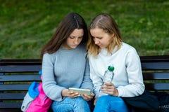 Étudiante de deux écolières En été ils se reposent sur un banc Ils se reposent après école en nature Mains tenant une bouteille d photos libres de droits
