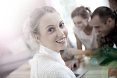 Étudiante de jeune femme entre autres étudiants ayant l'amusement Photo stock