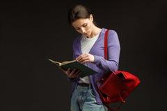 Étudiante de lecture avec les livres et le sac à dos Photos stock
