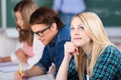 Étudiante de pensée Sitting With Classmates photographie stock