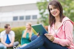 Étudiante de sourire à l'aide de la tablette avec des étudiants dans le parc Image stock