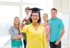 Étudiante de sourire avec le diplôme et le coin-chapeau Photos libres de droits