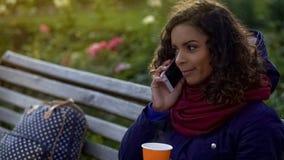 Étudiante de sourire parlant au-dessus du téléphone, prenant le rendez-vous avec des amis Images stock