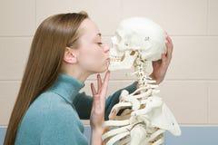 Étudiante embrassant un squelette humain Image stock