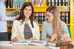 Étudiante With Friend Sitting à l'université Photo libre de droits