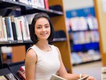 Étudiante heureuse à la bibliothèque photos libres de droits