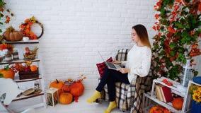 Étudiante Holding Folder et travail de lecture, séance dans la chaise contre photographie stock libre de droits